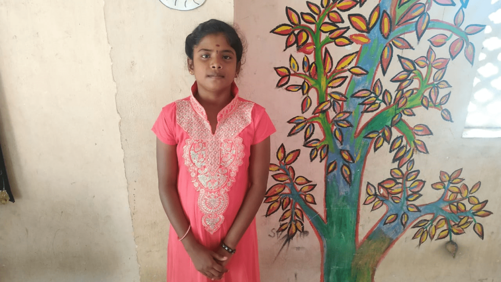 kavipriya standing next to a wall art