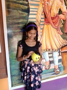 Ruchita smiling looking at her piggy bank.