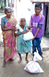 Periyakka receiving hope for the elderly rationing kits from a Hope student