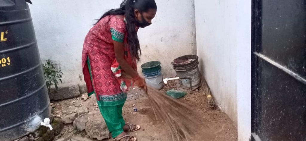 Hope Student Yazhini sweeping her backyard.